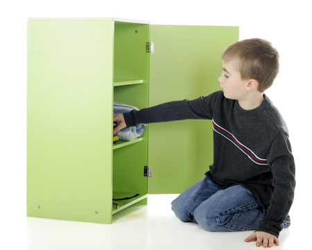 A young elementary boy pulling sneakers from his small locker.  On a white background. 写真素材