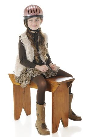 riding helmet: Una ni�a de primaria muy feliz sentado en su casco de montar y botas, mientras que straddeling un banco como a su caballo. Sobre un fondo blanco.
