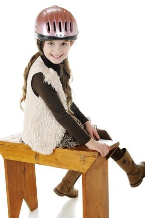 riding helmet: Un jinete a caballo muy joven en busca de regresar de un viejo banco, mientras que en su casco de montar y botas. Sobre un fondo blanco.