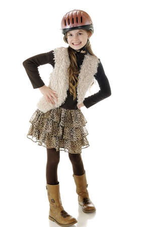 A beautiful elementary girl looking sharp and sassy in her horsoe-riding helmet and boots.  On a white background. Stock Photo - 13269402
