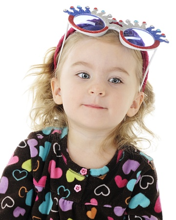 An adorable preschool girl wearing silly sunglasses on her head.  On a white background. Stock Photo - 13370180