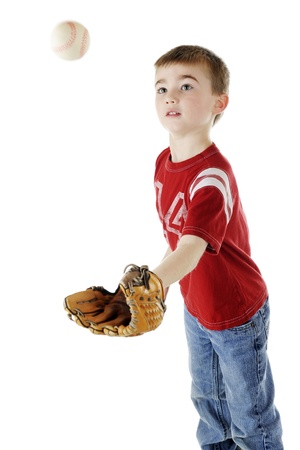 A young elementary boy stretching to catch a coming baseball.  Motion blur on ball.  On a white background. photo