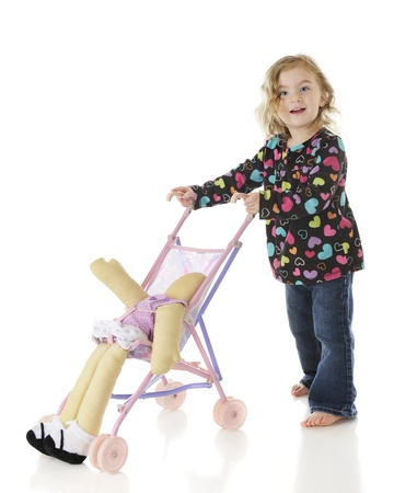An adorable preschooler pushing her doll yin an umbrella stroller, but the doll is slipping out   On a white background  Stock Photo