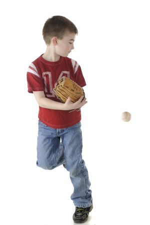A young elementary boy looking back while running with his baseball mitt   The ball  with motion blur  behing him   On a white background  photo