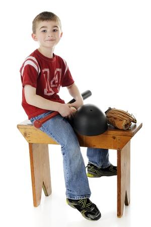 Een jonge elementaire jongen gelukkig weerszijden van een kleedkamer bank met zijn bat, bal-, veiligheids-en helmt mitt Op een witte achtergrond