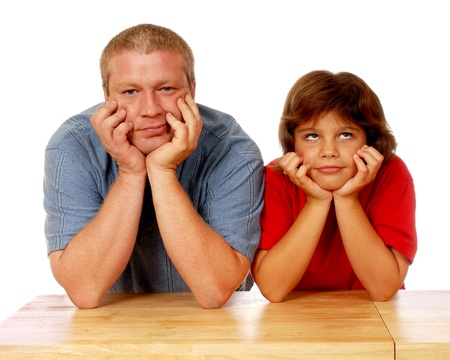 thinkers: Head and shoulders image of a father and elementary daughter thinking with their head on their hands   On a white background  Stock Photo