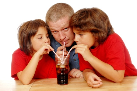 A father and his 2 daughters drinking from the same glass of soda with three different straws   On a white background