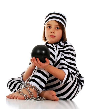 A sad young elementary prisoner with a ball and chain and a black and white striped uniform   On a white background