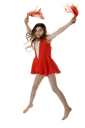 A pretty elementary cheerleader jumping with her red and white  pompoms   Motion blur on hands and pompoms   On a white background  photo