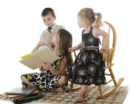 Three siblings discussing a book the oldest child is reading   On a white background  photo