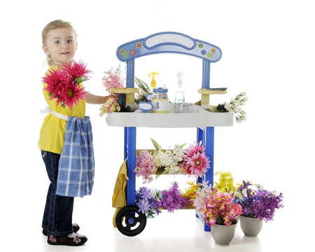 An adorable preschooler handing a bouquet out to the viewer from her flower stand   The stand