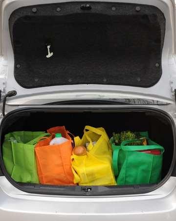 Four colorful eco-friendly shopping bags filled mostly with groceries in the opened trunk of a car