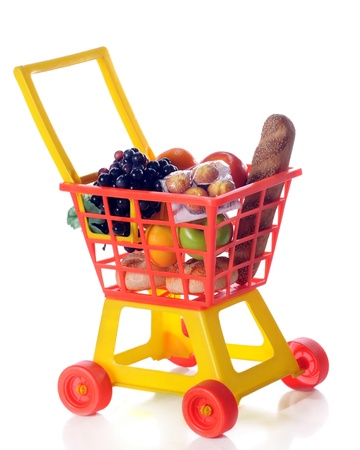 A colorful toy shopping cart filled with groceries   Isolated on white  photo