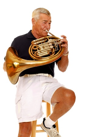 A senior man playing his French horn    Stock Photo