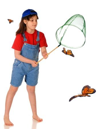 overol: Una niña descalza primaria persiguiendo mariposas monarca con una red aislada en blanco Foto de archivo