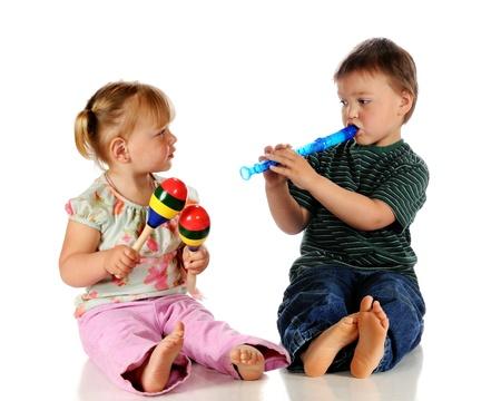 그녀는 흰색에 고립 마라카스를 재생하는 동안 그의 여동생에 레코더를 연주 유치원 소년 스톡 콘텐츠