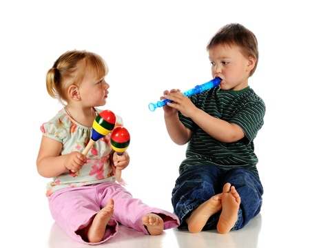 A preschool boy playing the recorder to his sister while she plays the maracas   Isolated on white