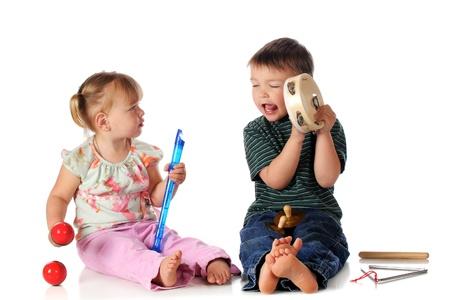 pandero: Un ni�o en edad preescolar cantando y tocando la pandereta, mientras que su hermanita mira aislado en blanco Foto de archivo