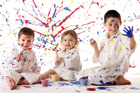 Three young siblings in white paint spattered smocks painting in primary colors on white    Stockfoto