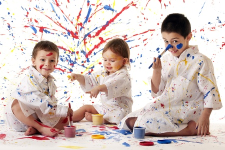 Three young siblings in paint-spattered white smocks, having fun painting in primary colors on white