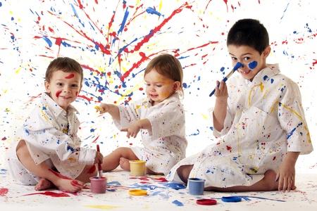 niños pintando: Tres hermanos jóvenes en las salpicaduras de pintura, pintura de batas blancas que se divierten en los colores primarios sobre fondo blanco
