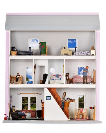 A family of five working and playing inside a furnished doll house  Stock Photo