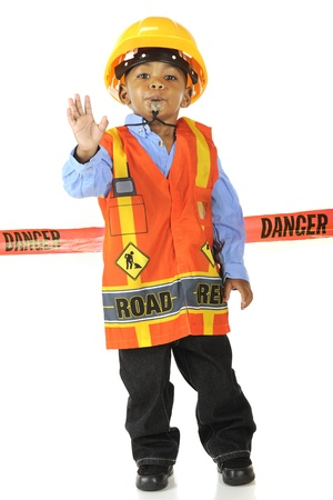 An adorable young road worker blowing a whistle and gesturing  Stop   in his safety vest and hard hat   He stands in front of a red  Danger  tape  Stock Photo