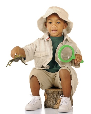 An adorable preschooler sitting on a tree stump in safari attire   He