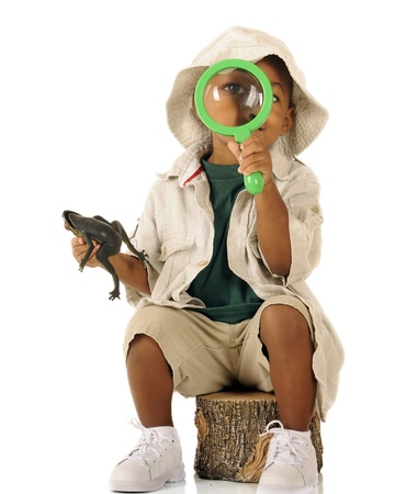 An adorable preschooler looking at the viewer through a magnifying glass   He photo