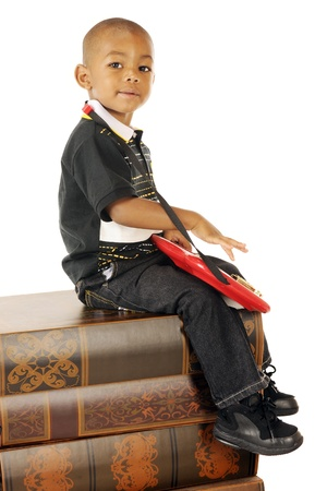 An adorable preschool boy playing a toy electric guitar on a stack of huge books    photo