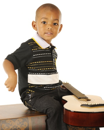 A handsome preschooler happily playing guitar on a white background