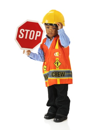 An adorable preschooler in  Road Crew  gear holding a stop sign   Isolated on white  photo