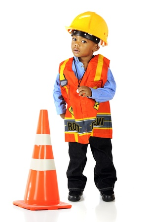 road construction: An adorable preschooler in road crewman safety gear by a an orage traffic cone   Isolated on white