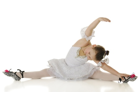 gracefully: A young elementary ballerina gracefully stretching in her dance costume   On a white background  Stock Photo