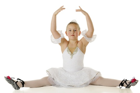 An elementary aged ballerina doing the splits gracefully in her dance costume   On a white background  photo
