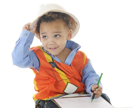 An adorable 2-year-old wiring on a clip board in his construction garb   On a white background  photo
