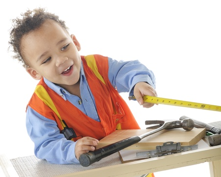 An adorable 2-year-old  construction worker  happily taking measurements   On a white background  photo