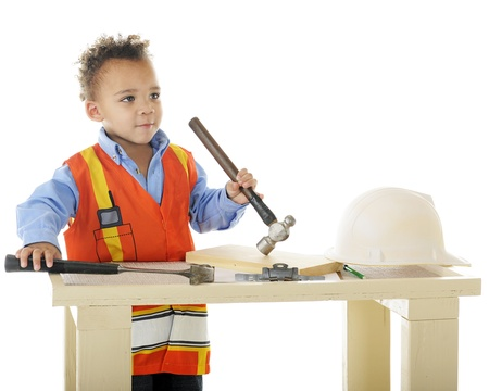 A biracial preschool  construction worker  standing at his workbench holding two hammers   On a white background Stock Photo - 13531522