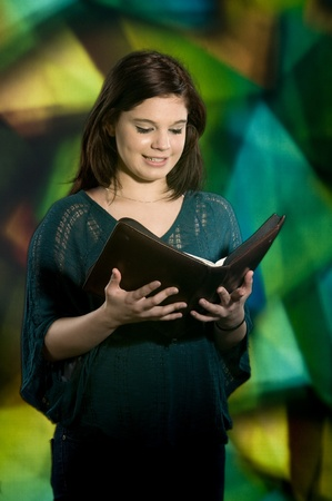 A young teen smiling as she reads her Bible in front of a large stained glass window    photo