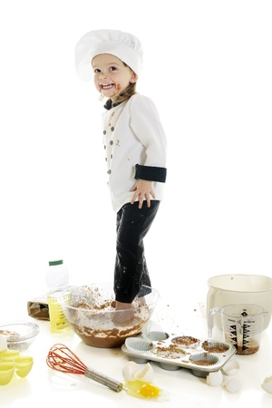 stepping: An adorable preschooler  chef  happily stepping in her chocolate cake batter that Stock Photo