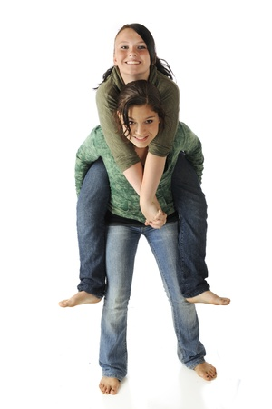 Een aantrekkelijke jonge tiener geeft haar fiiend een piggyback rit Geïsoleerd op wit Stockfoto