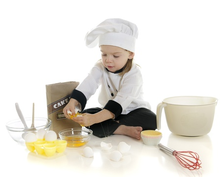 An adorable preschool  chef  cracking eggs as she makes her first cake   On a white background  photo
