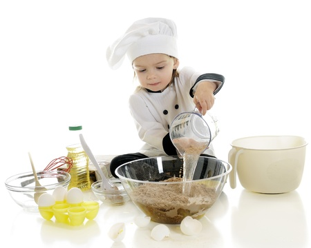 An adorable preschool  chef  dumping water from a measuring cup into the chocolate cake mix in a clear bowl