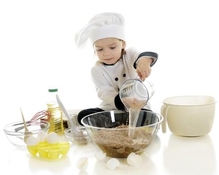 gorro chef: Un chef adorable preescolar vertido de agua de una taza de medir en la mezcla de pastel de chocolate en un recipiente transparente
