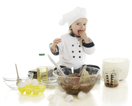 An adorable preschool  chef  tasting a fistful of the chocolate cake batter that she photo
