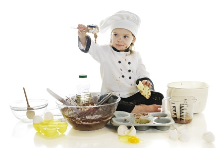 A beautiful preschool  chef  playing in the batter of her first cake   On a white background  photo