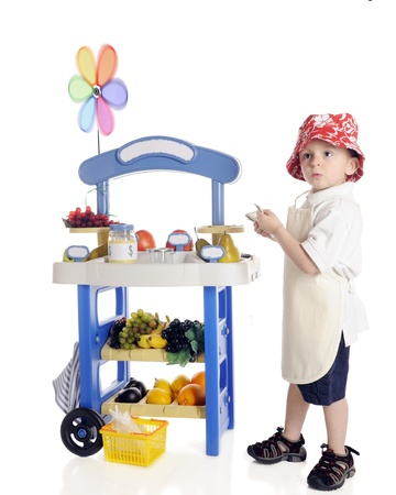 inquisitively: A serious preschool  vendor  looking inquisitively away from his fruit stand with several dollar bills in his hand   The stand