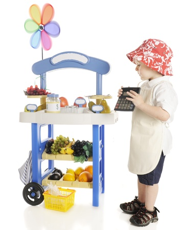 An adorable preschooler holding his calculator while looking over the produce on his fruit stand   Signs left blank for your text   On a white background Stock Photo - 13586663