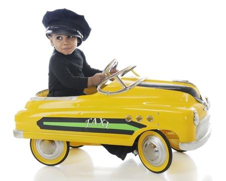 taxista: Un niño feliz conduciendo un coche de pedales taxi en hiw taxista sombrero sobre un fondo blanco