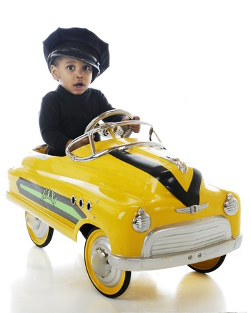A toddler cab driver wering a cabbie hat and driving a yellow pedal-car taxi   On a white background